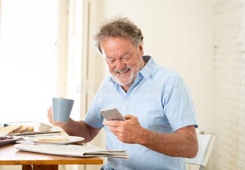 De knappe oudste trok de oude mens terug thuis gebruikend mobiele telefoon met vreugde terwijl het hebben van ontbijt royalty-vrije stock afbeelding