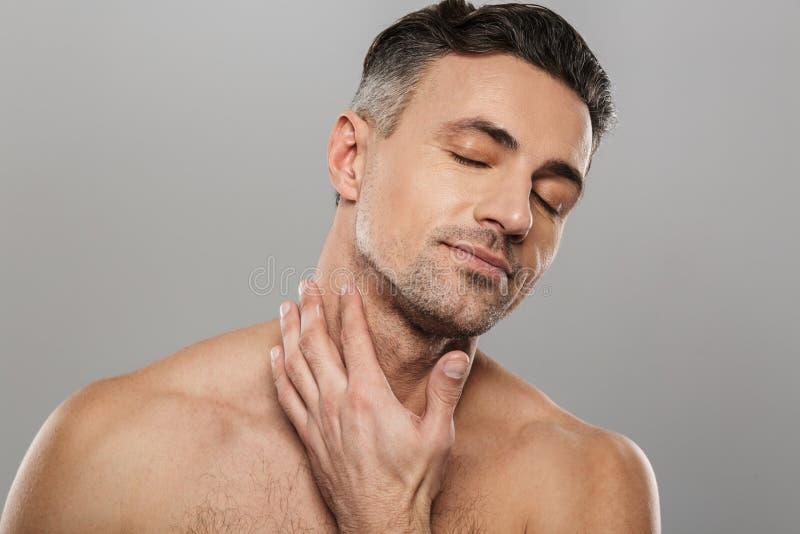 De knappe rijpe mens behandelt zijn huid met room stock foto