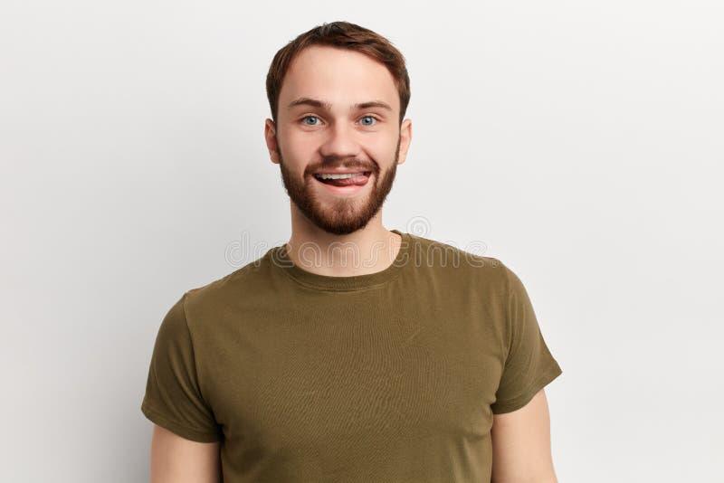 De knappe speelse jonge mens draagt groene t-shirt, toont tong stock fotografie