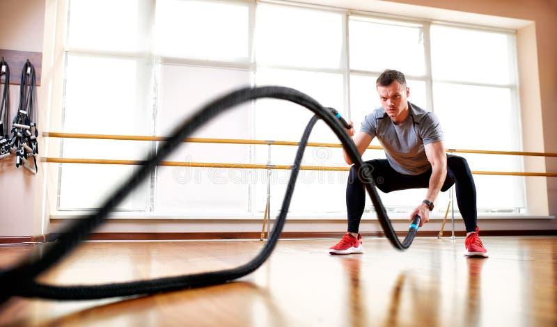 De knappe spiermens doet de oefening van de slagkabel terwijl het uitwerken in gymnastiek stock afbeeldingen