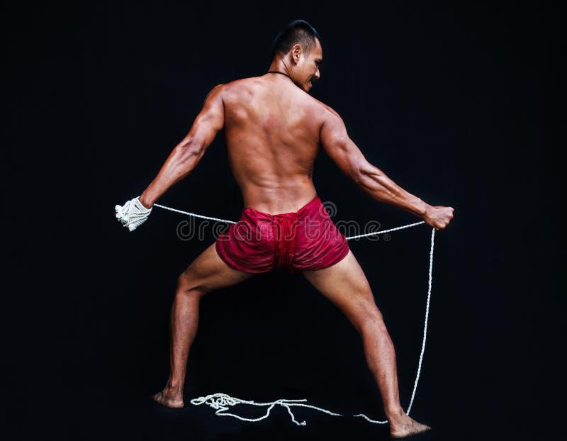 De knappe Spiermens toont oude Aziatische traditionele vechtsporten, het Thaise In dozen doen of Muay Thai royalty-vrije stock fotografie