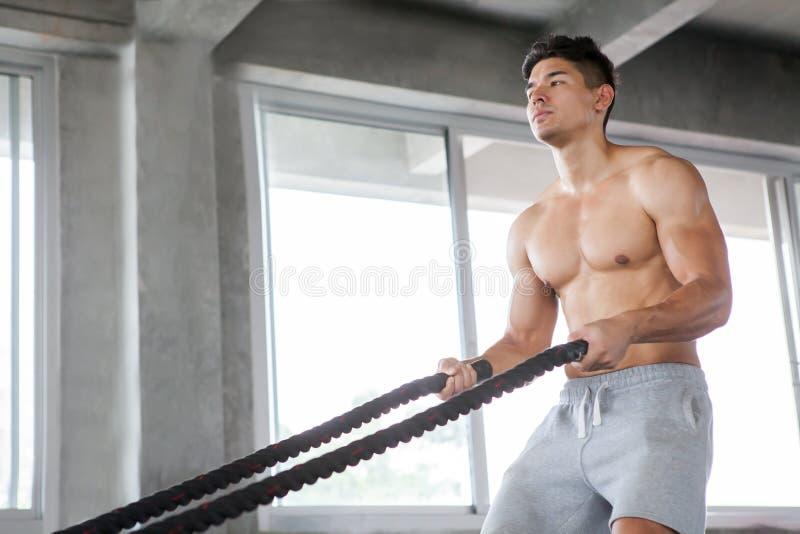de knappe Spieroefeningen van de bodybuildermens met slagkabels bij gymnastiek Shirtless fitness jonge sportmens opleiding Werk u stock afbeelding