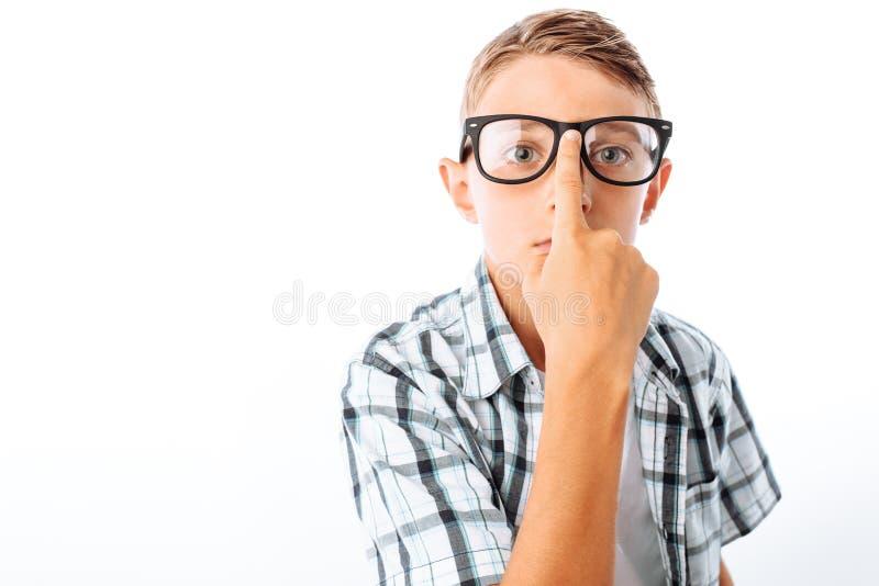 De knappe tienerjongen maakt glazen, mannetje nerd in Studio op witte achtergrond recht stock foto's