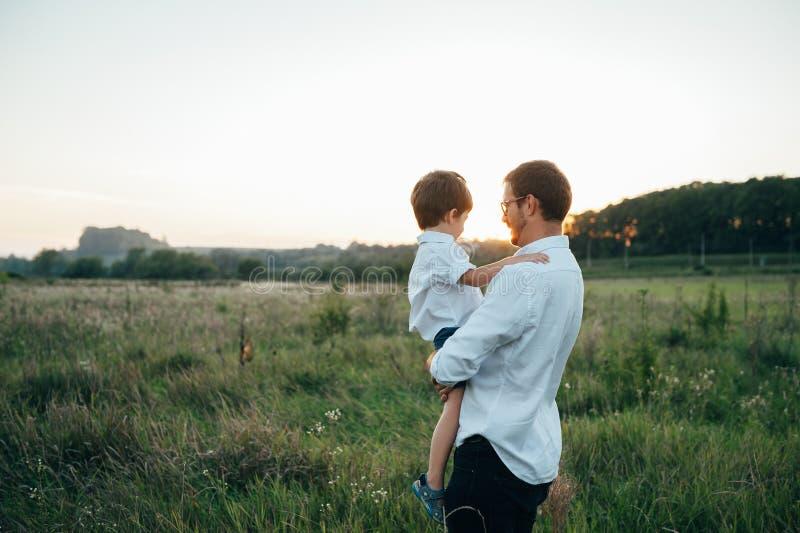 De knappe vader met zijn kleine schattige zoon heeft plezier en speelt op de groene grasgras. Gefeliciteerd gezinsconcept. Schoonh stock afbeeldingen