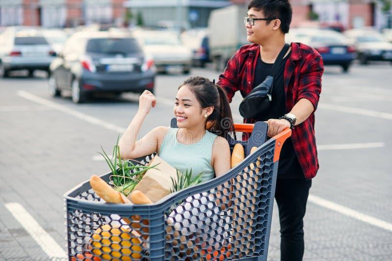 De knappe vietnamese jongen en het mooie meisje gaan uit winkelcentrum en verhuizen naar hun auto Grappig familiewinkelen stock foto