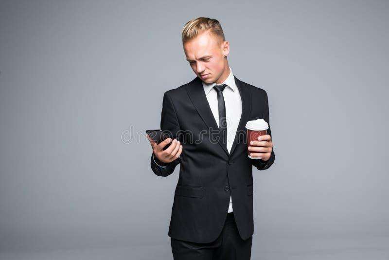 De knappe zakenman in formeel kostuum gebruikt een slimme telefoon, houdend een kop van koffie op grijze achtergrond stock afbeelding