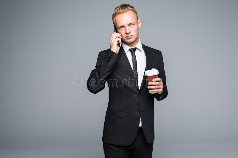 De knappe zakenman in formeel kostuum gebruikt een slimme telefoon, houdend een kop van koffie op grijze achtergrond stock foto