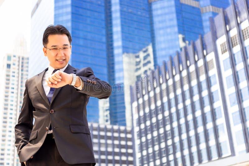 De knappe zakenman kijkt polshorloge voor het controleren van tijd CH stock foto