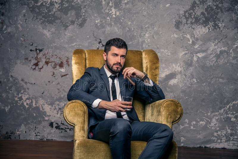 De knappe knappe zakenman neemt een rust zitting op de stoel en het drinken van wisky met een sigaar en het denken wearing stock fotografie