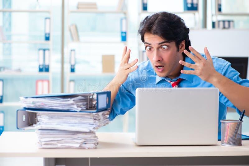 De knappe zakenman ongelukkig met het bovenmatige werk in het bureau royalty-vrije stock foto