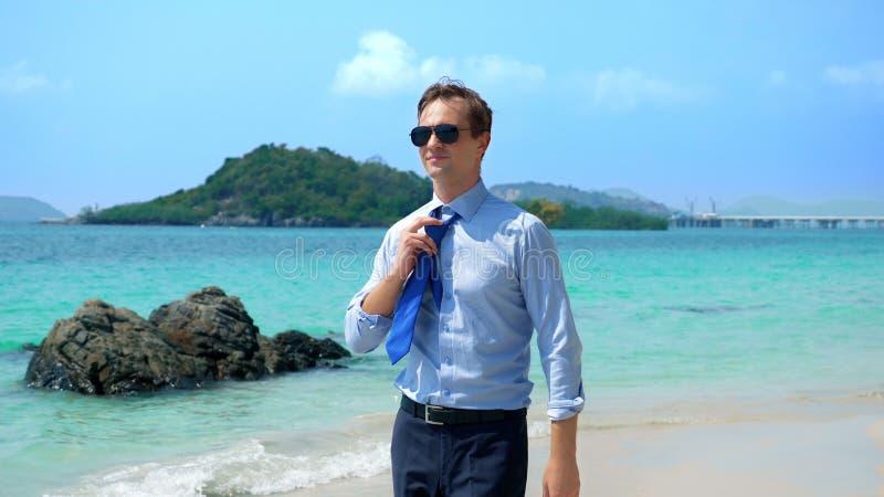 De knappe zakenman in zonnebril liep langs een tropisch strand, die zijn band opstijgen royalty-vrije stock foto