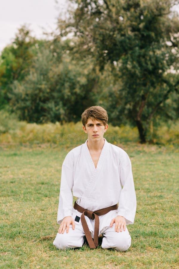 De knappe zitting van de karatestudent op een natuurlijke achtergrond Oostelijk het vechten lessenconcept De ruimte van het exemp stock afbeeldingen