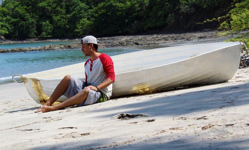 De knappe zitting van de schipbreukelingmens in het strand door een gesloopte boot die op hulp met oceaan en wildernis op de acht stock afbeelding