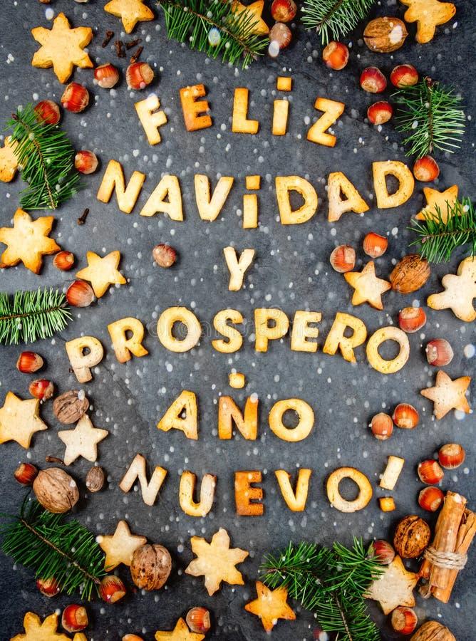 DE KOEKJES VAN FELIZ NAVIDAD Vrolijke Kerstmis en Gelukkig Nieuwjaar het Engelse Spaans met gebakken koekjes, Kerstmisdecoratie v stock afbeeldingen