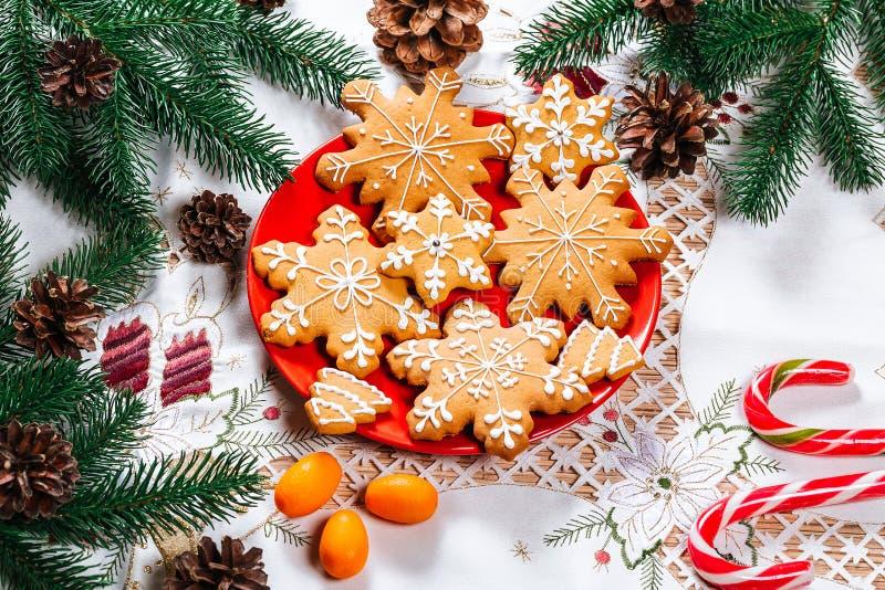 De koekjes van de Kerstmispeperkoek eigengemaakt op rode plaat met branche royalty-vrije stock afbeeldingen