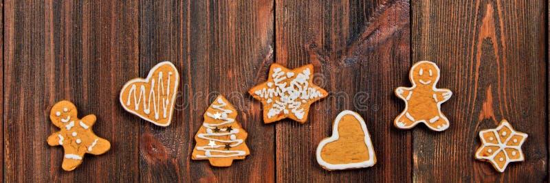 De koekjes van de Kerstmispeperkoek van verschillende vormen op een bruine houten lijst De ruimte van het exemplaar stock fotografie