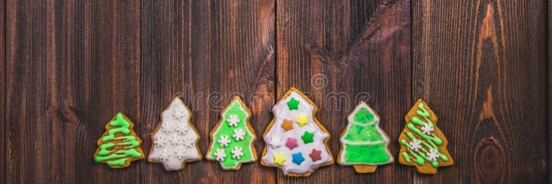 De koekjes van de Kerstmispeperkoek in de vorm van Kerstbomen op een bruine houten lijst De ruimte van het exemplaar stock fotografie