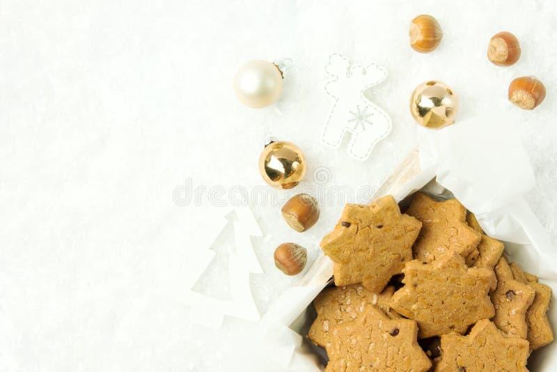 De koekjes van de Kerstmiszandkoek met hazelnoten in stervorm in houten doos Witte de herten gouden ballen van de ornamentenspar  stock foto