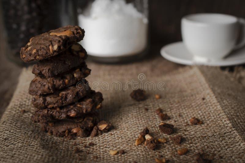 De koekjeschocolade van cashewnoot wordt erachter geschikt op een zak de kop van koffie, fles bloem, fles koffie royalty-vrije stock fotografie