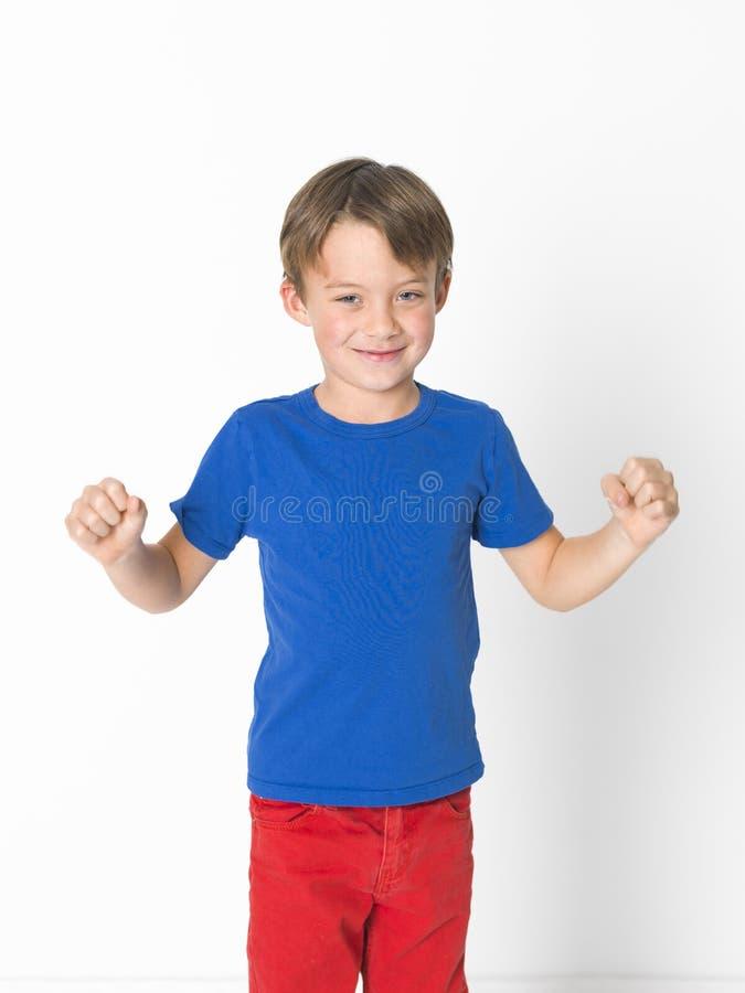 De koele en leuke zes éénjarigenjongen in rode broeken en blauw overhemd stelt voor witte achtergrond royalty-vrije stock fotografie