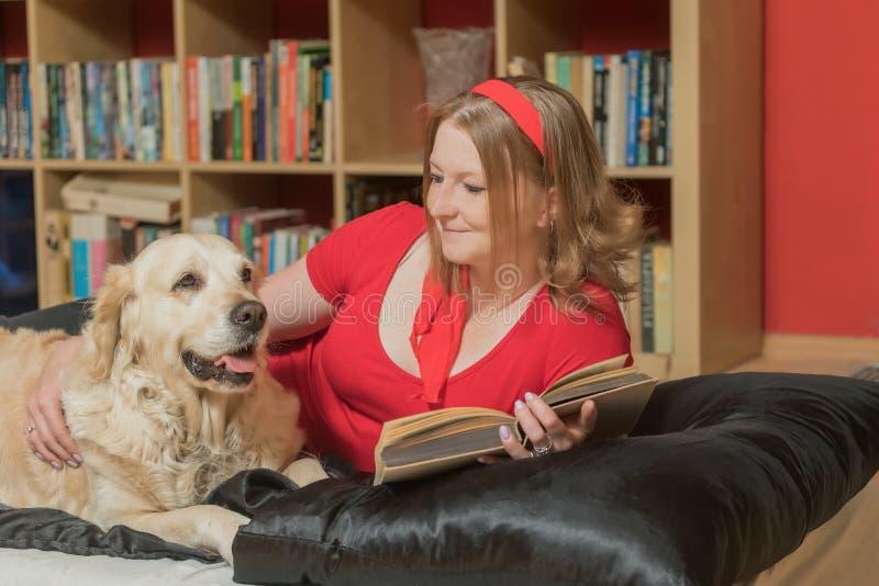 De koele jonge vrouw ontspant met een hond en een boek stock foto's