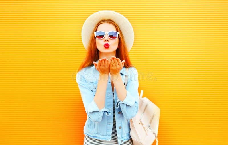 De koele meisjes jonge vrouw verzendt een luchtkus op oranje achtergrond royalty-vrije stock foto