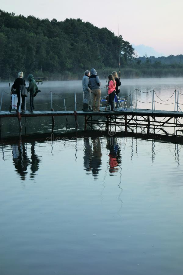 De koele stille avond van mensenenjoyinga bij een meer stock afbeelding
