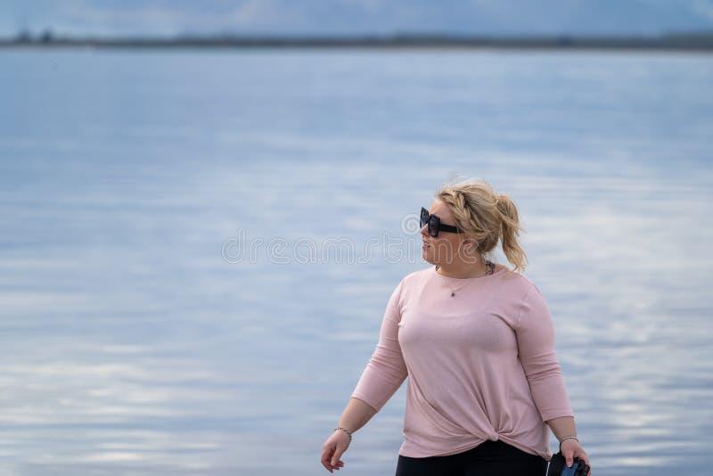 De koele, toevallige vrouw kijkt weg in de afstand van een meer, die toevallige kleding met gevlecht updokapsel dragen stock foto's