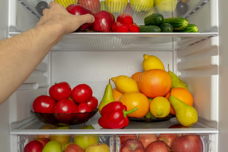De koelkast wordt gevuld met groenten, vruchten De hand neemt voedsel van de ijskast stock afbeelding