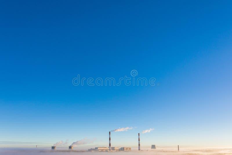 De koeltorens en de pijpen van thermische krachtcentrale in de duidelijke de herfst zonnige dag stock foto's