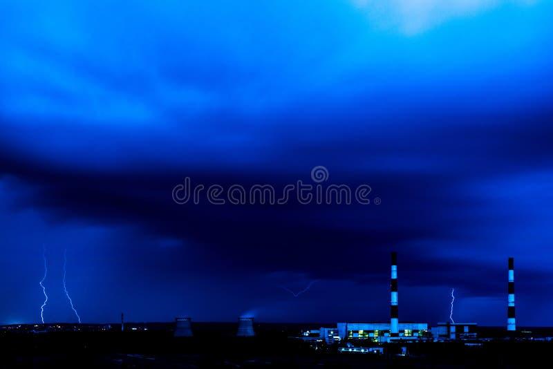 De koeltorens van thermische krachtcentrale in de regenachtige nacht met de bliksem stock afbeeldingen