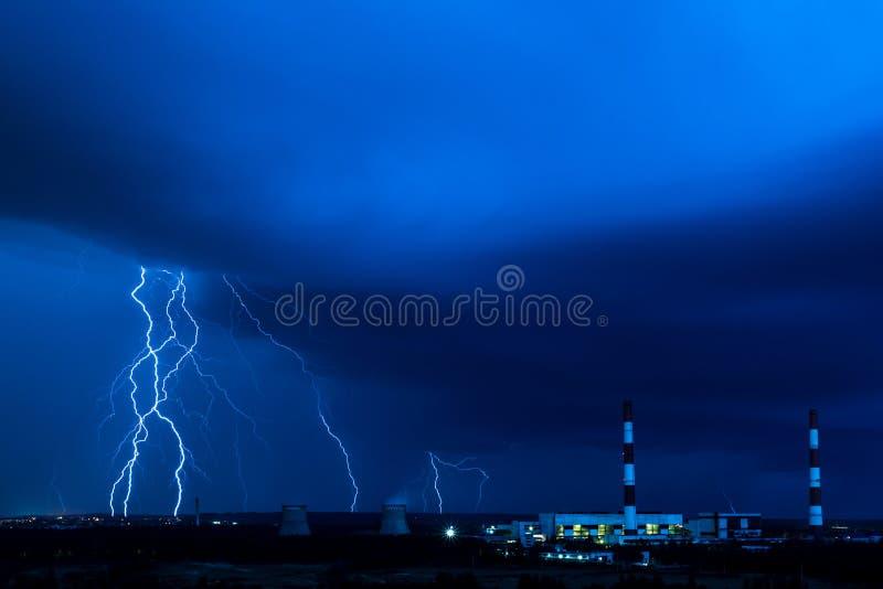 De koeltorens van thermische krachtcentrale in de regenachtige nacht tijdens het onweer met de bliksem stock afbeeldingen