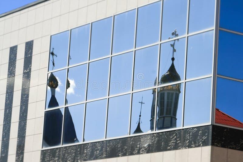 De koepels van de Orthodoxe kerk worden weerspiegeld in het glas van het gebouw royalty-vrije stock afbeeldingen