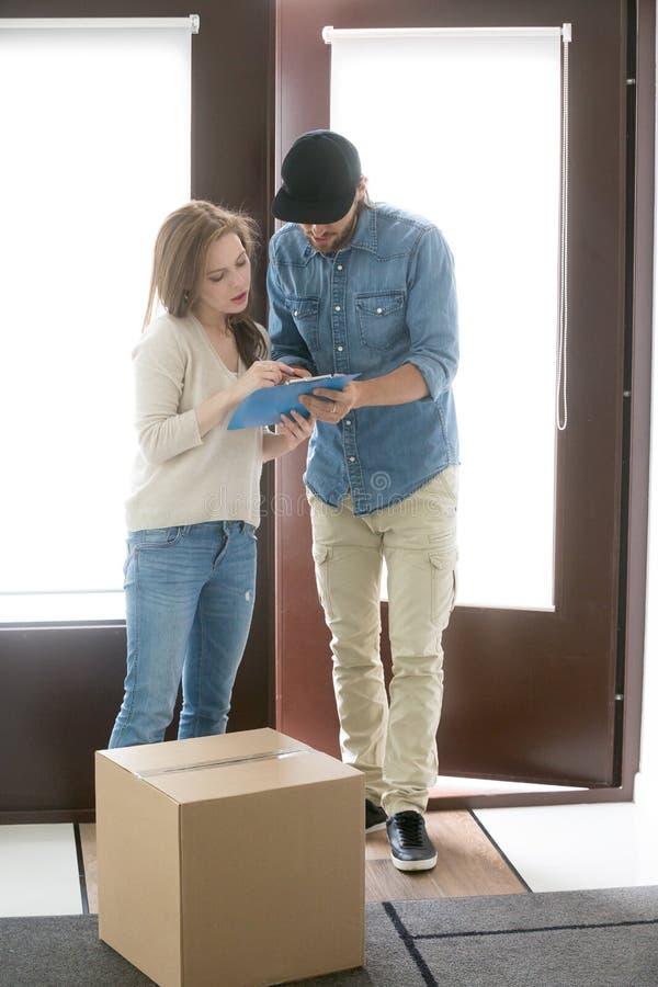 De koerier brengt een pakket aan de klantenvrouw royalty-vrije stock foto