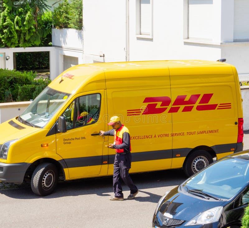 De koerier gaat DHL gele leveringsbestelwagen na het leveren van het op tijd het leveren pakketpakket in royalty-vrije stock fotografie