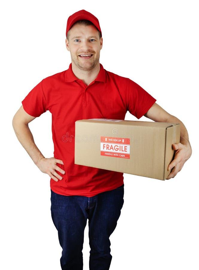 De koerier van de leveringsdienst in rode eenvormig met breekbare verzendingsdoos die op wit wordt geïsoleerd stock afbeeldingen