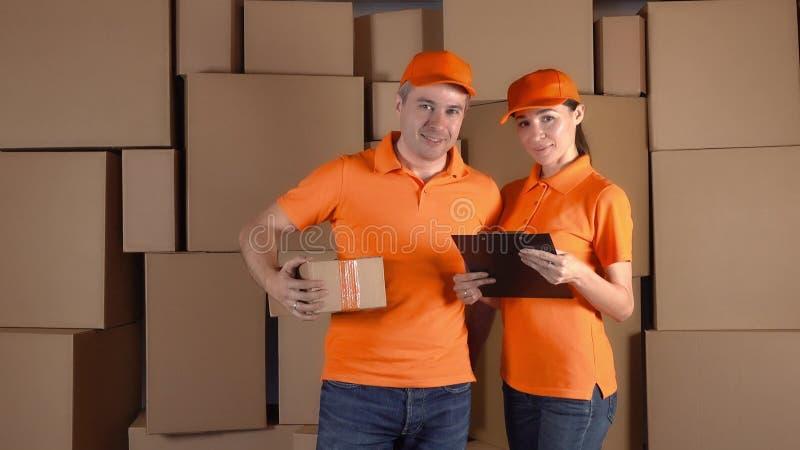 De koeriers in oranje eenvormige status tegen bruin karton stapelt backround Het personeel van het leveringsbedrijf stock afbeelding