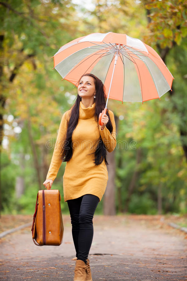 De koffer en de paraplu van de meisjesholding stock afbeelding