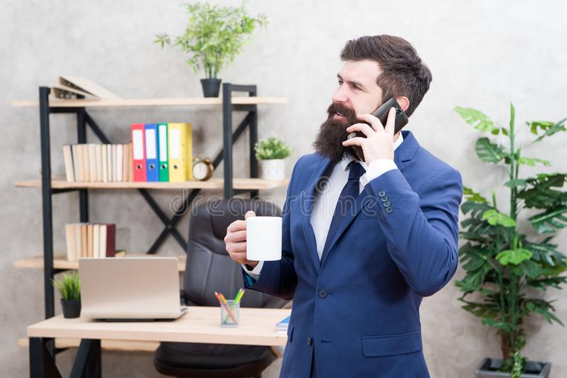 De koffie is belofte van succesvolle onderhandelingen Gewijde cafe?ne De greepkop en smartphone van de mensen gebaarde zakenman m royalty-vrije stock foto's