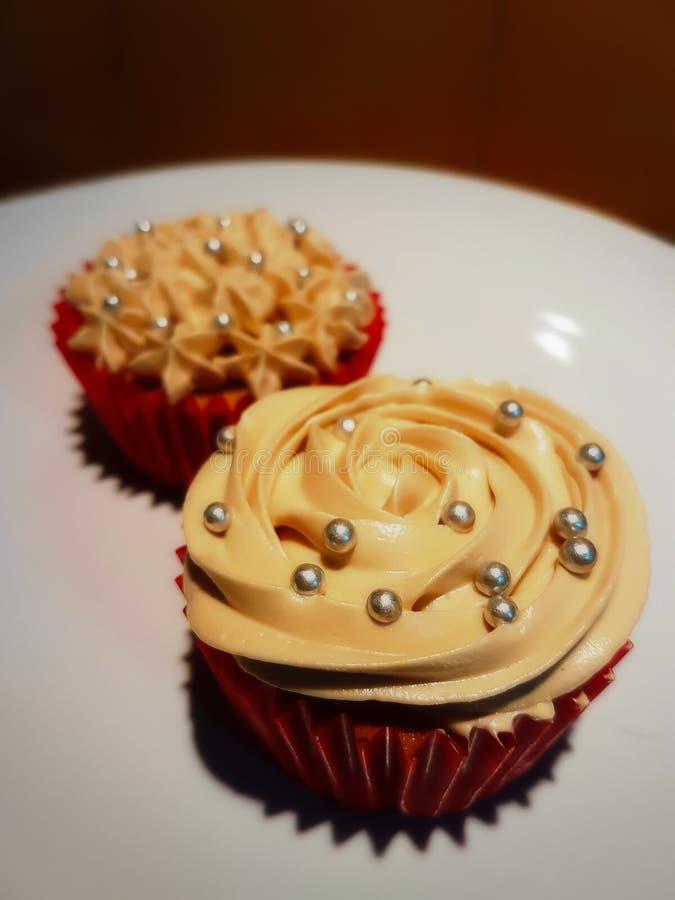 De koffie cupcakes in rode die document koppen met koffieroom worden verfraaid nam en zilveren suikerkorrel op bovenkant toe stock fotografie