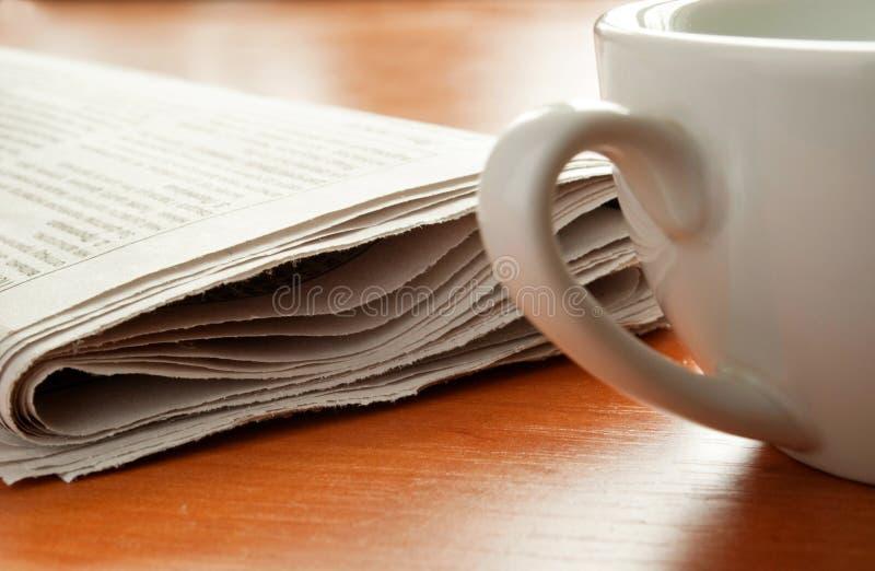 De koffie en de krant van de ochtend. stock fotografie