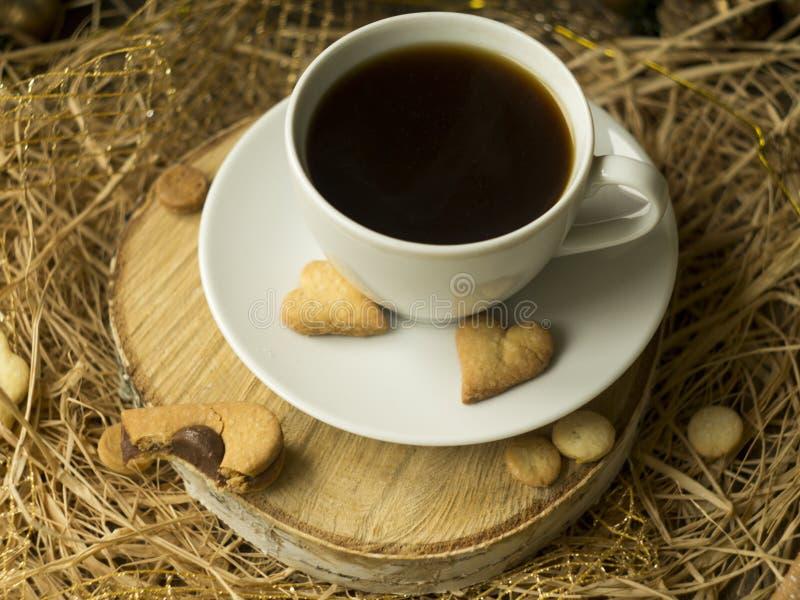 De koffie en een hart vormden koekje op een houten zaag op een zwarte achtergrond Ontbijt voor haar op de Dag van Valentine Cooki stock foto