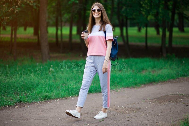 De koffie gaat  Mooie jonge vrouw in zonnebril die koffiekop houden en terwijl het lopen glimlachen stock afbeelding