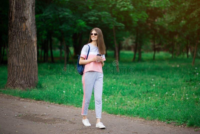 De koffie gaat  Mooie jonge vrouw in zonnebril die koffiekop houden en terwijl het lopen glimlachen royalty-vrije stock afbeelding