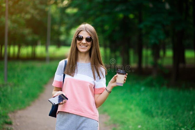 De koffie gaat  Mooie jonge vrouw in zonnebril die koffiekop houden en terwijl het lopen van straat glimlachen royalty-vrije stock foto's