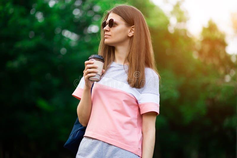 De koffie gaat  Mooie jonge vrouw in zonnebril die koffiekop houden en terwijl het lopen van straat glimlachen royalty-vrije stock afbeeldingen