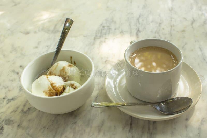 De koffie met melk en roomijsballen in witte koppen met lepels op een marmeren lijstoppervlakte sluit omhoog stock fotografie
