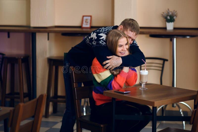 In de koffie, ontmoet een man een vrouw, koestert een kerel een meisje, zijn zij gelukkig om een vriend van een vriend, een jonge stock fotografie