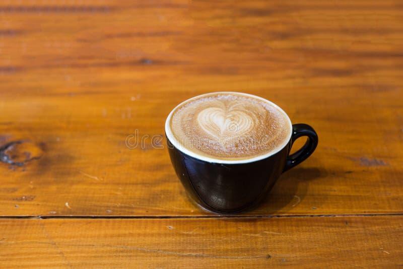 De koffie van de Lattekunst op houten lijst royalty-vrije stock afbeelding