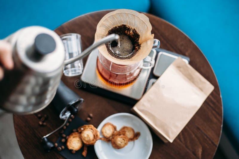 De koffie van de handdruppel, het gietende water van Barista op koffiedik met FI stock foto